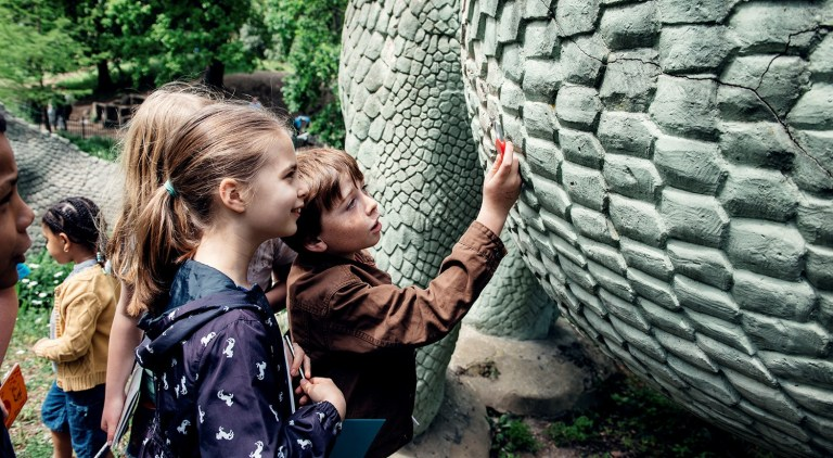 Kids with dinosaur sculptures